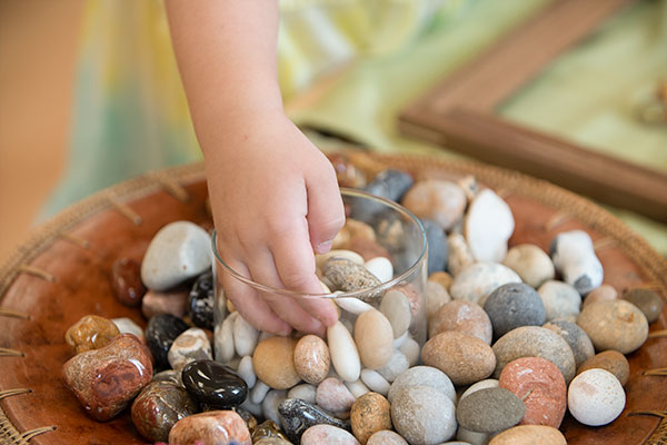 child touching polished stones and pebbles